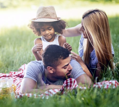 image of a family; mother and father laying on the grass with their baby overjoyed with their new Univeral Life Insurance Policy from the best insurance agency in Columbia, SC